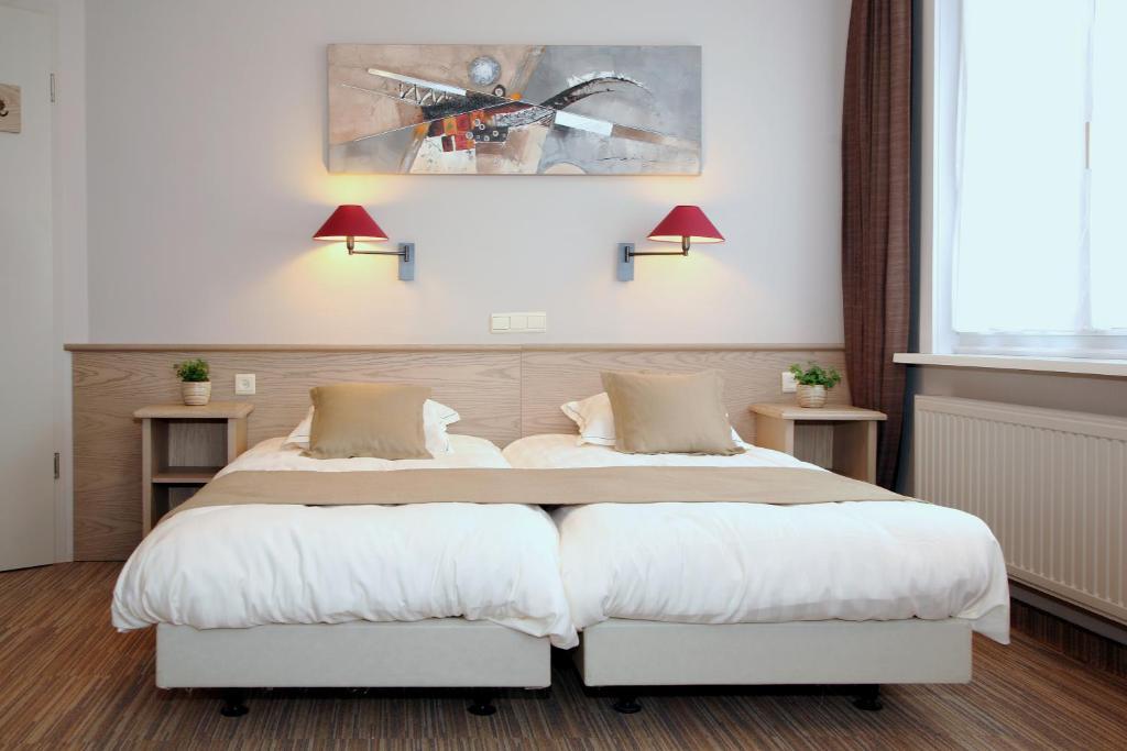 Een bed of bedden in een kamer bij Ambassador Hotel