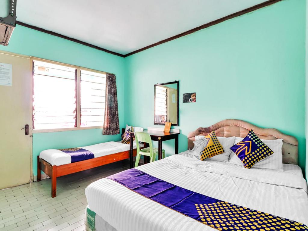 A bed or beds in a room at SPOT ON 90003 Villa Tawang