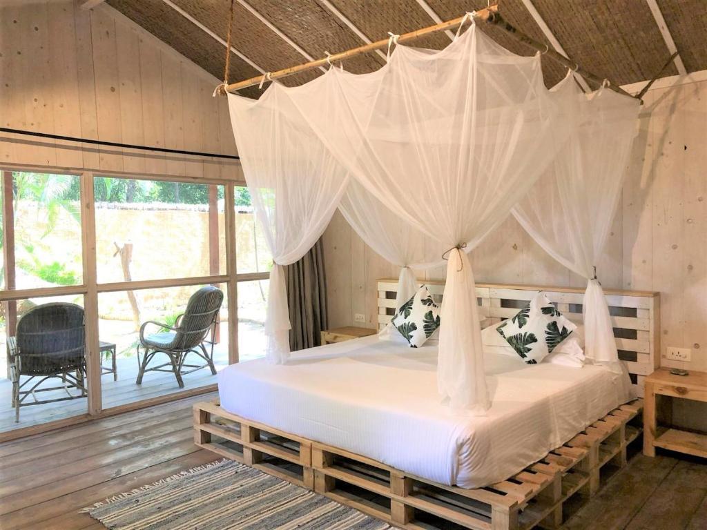 A bed or beds in a room at Palm Forest Palolem