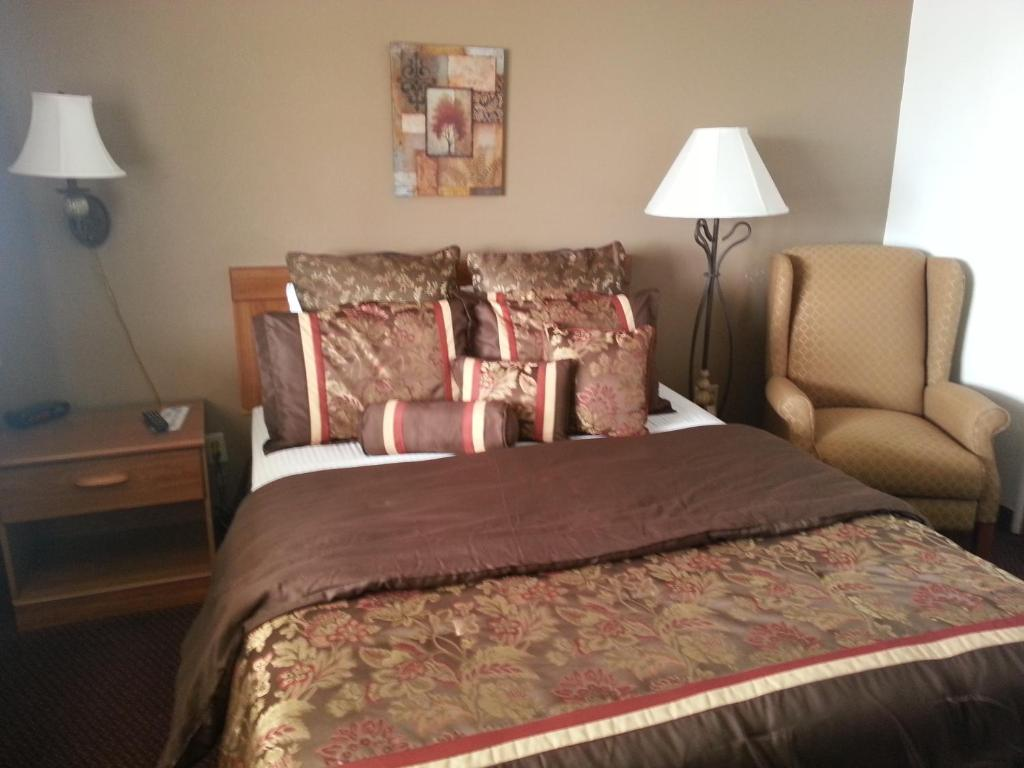 A bed or beds in a room at Raine Motel