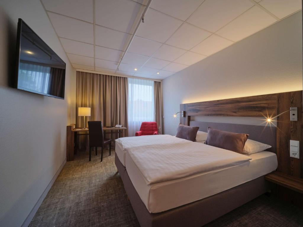 A bed or beds in a room at Best Western Hotel Prisma