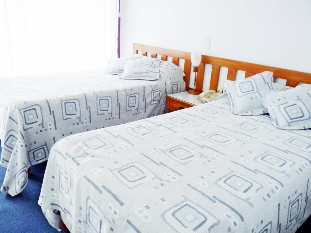 A bed or beds in a room at Hotel los Nogales