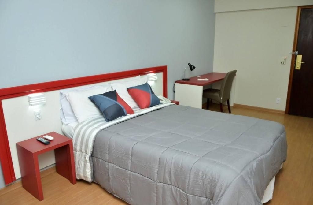 A bed or beds in a room at Embaixador Prime Hotel