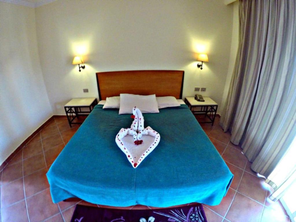 Een bed of bedden in een kamer bij Luna Sharm Hotel