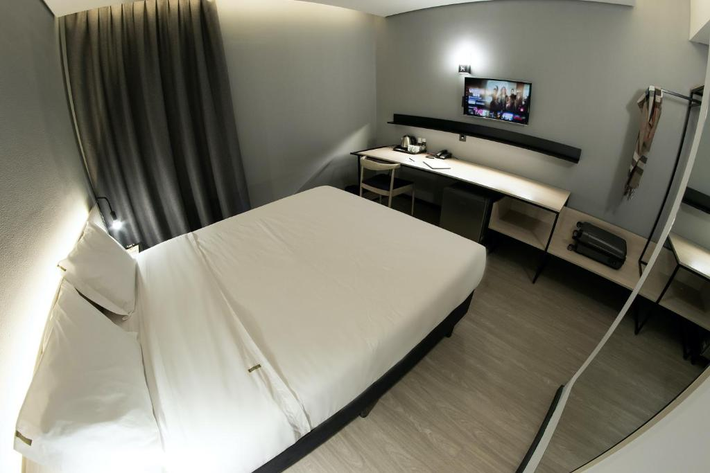 A bed or beds in a room at Naalt Hotel Joinville
