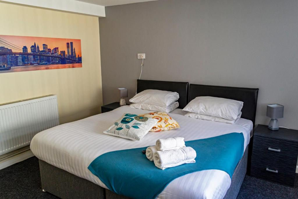 A bed or beds in a room at Lymedale Suites Studios & Aparthotel in NEWCASTLE UNDER LYME & STOKE