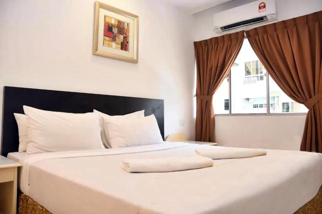 A bed or beds in a room at Promenade Service Apartment