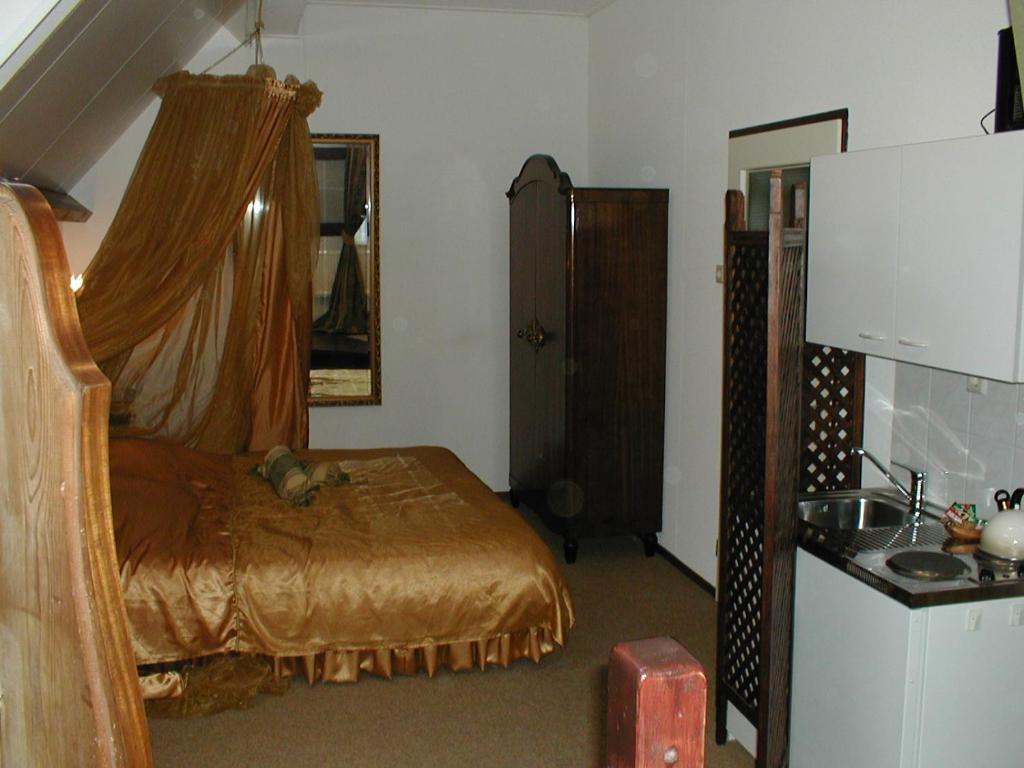 A bed or beds in a room at Hotel Hanzestadslogement De Leeuw in het centrum, Snoepwinkel, Hanzemuseum, Koffieschenkerij met Binnenplaats, Kamers met keukentje en Ontbijtservice