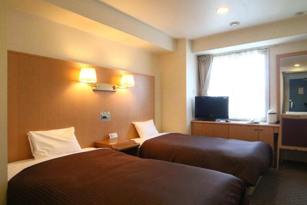A bed or beds in a room at Sapporo Classe Hotel