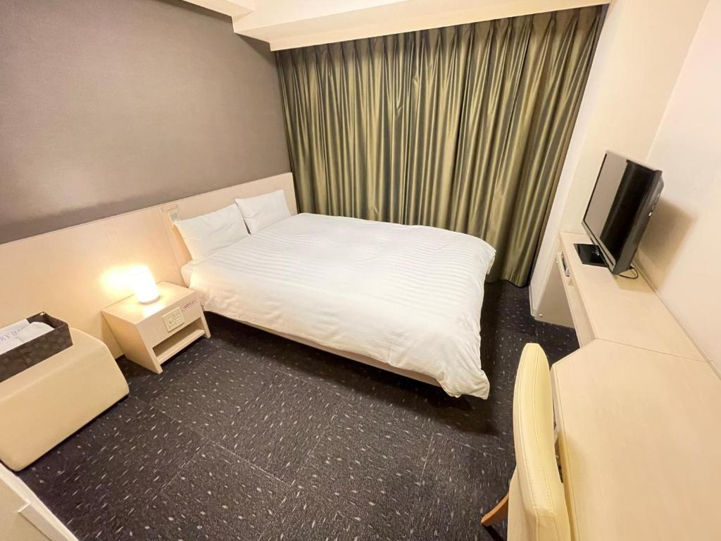 A bed or beds in a room at Dormy Inn Kitami
