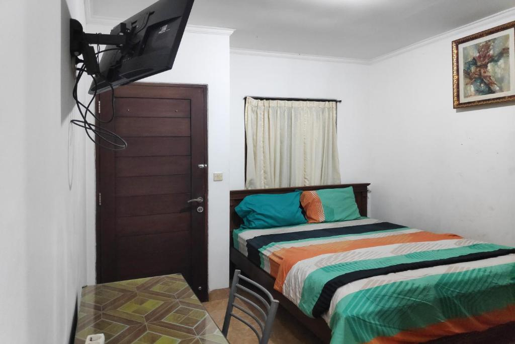 A bed or beds in a room at OYO 90274 Odah Guest House