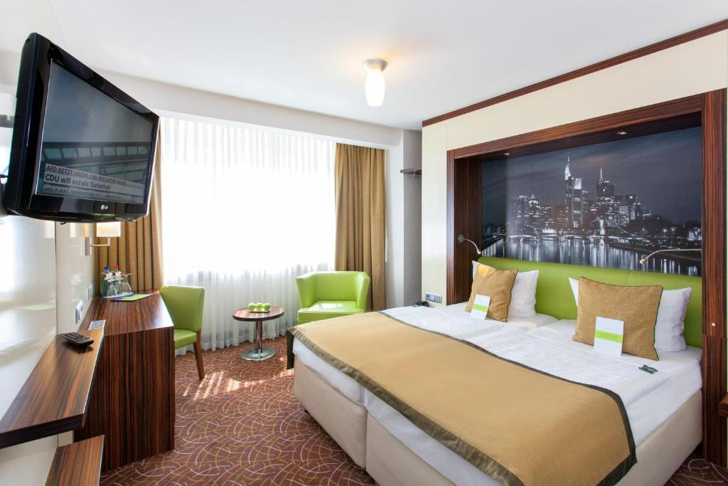 A bed or beds in a room at Hotel Scala Frankfurt City Centre