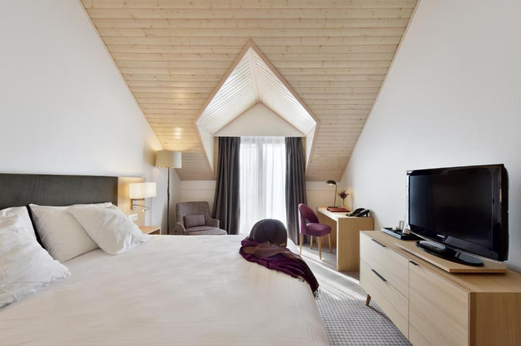 A bed or beds in a room at Hotel La Barcarolle