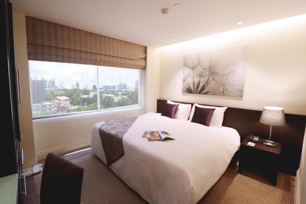 A bed or beds in a room at Siri Sathorn Bangkok by UHG