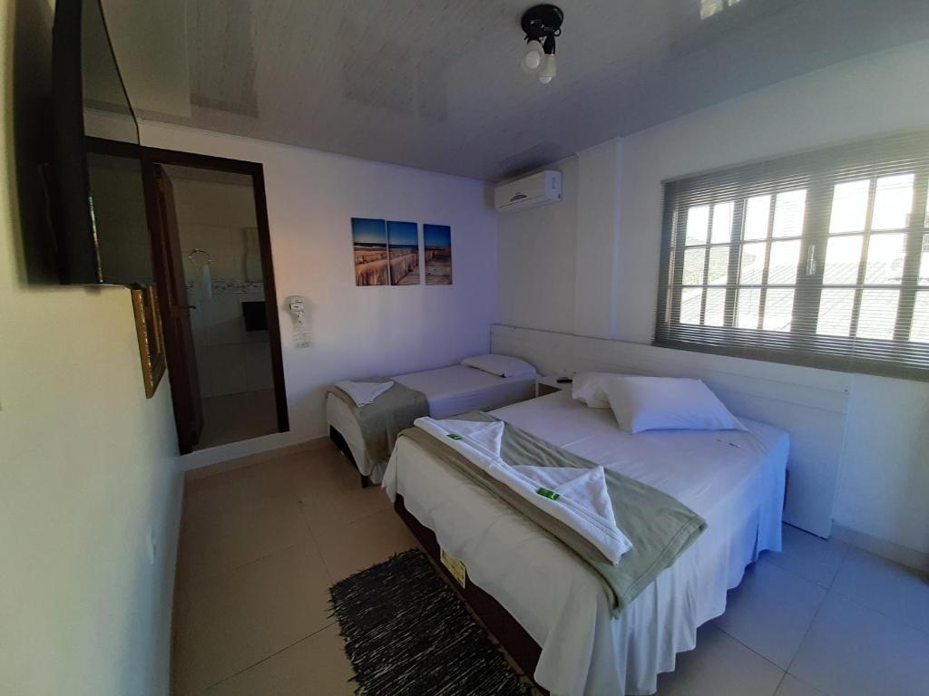 A bed or beds in a room at Pousada Casa do Luiggi