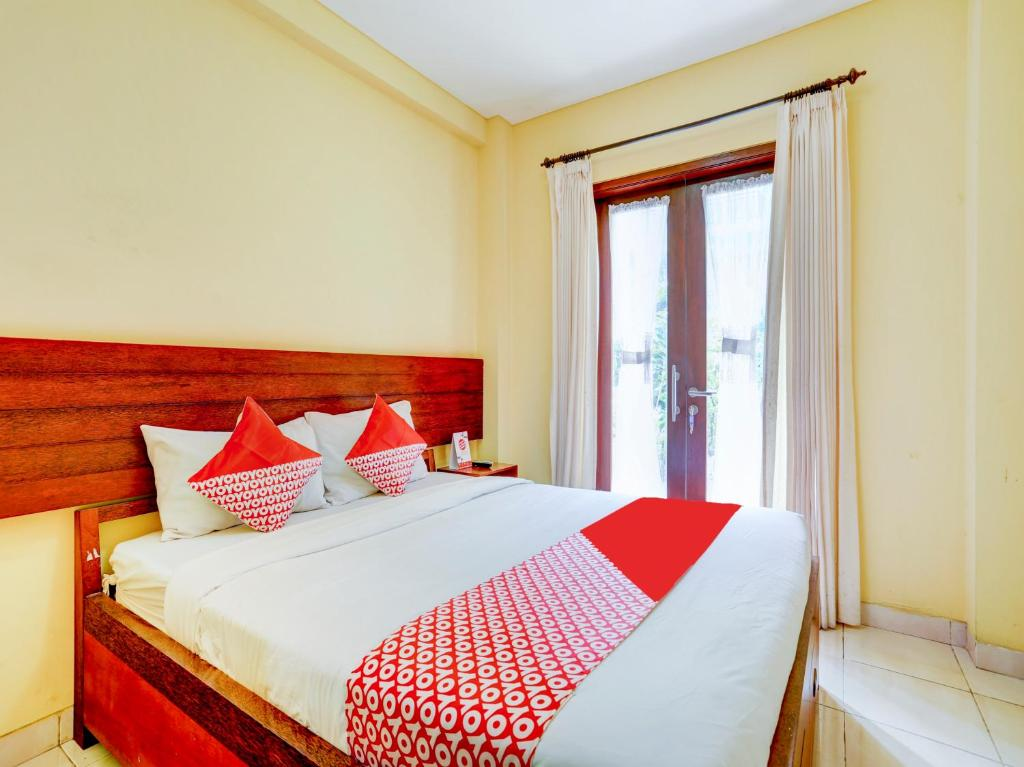 A bed or beds in a room at OYO 90311 Hotel Damai