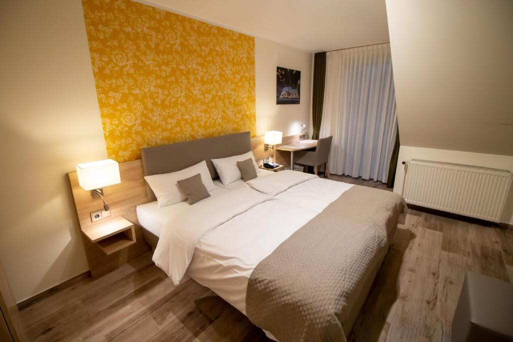 A bed or beds in a room at Hotel Fallersleber Spieker