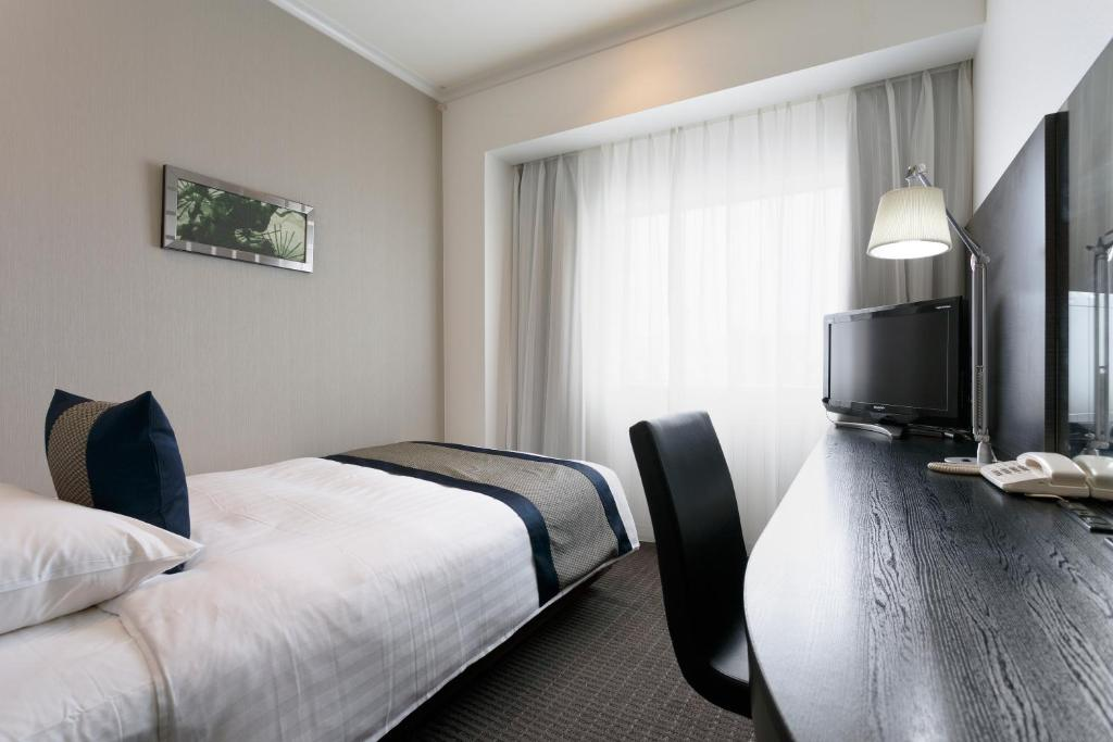 A bed or beds in a room at Palace Hotel Omiya