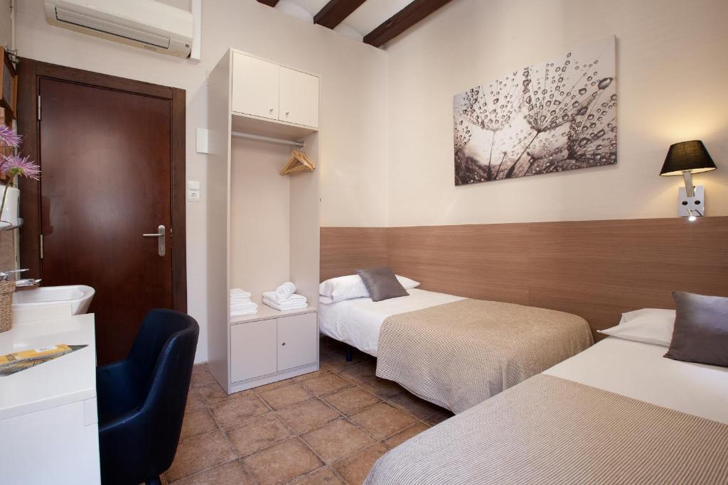 A bed or beds in a room at Pensión Mariluz