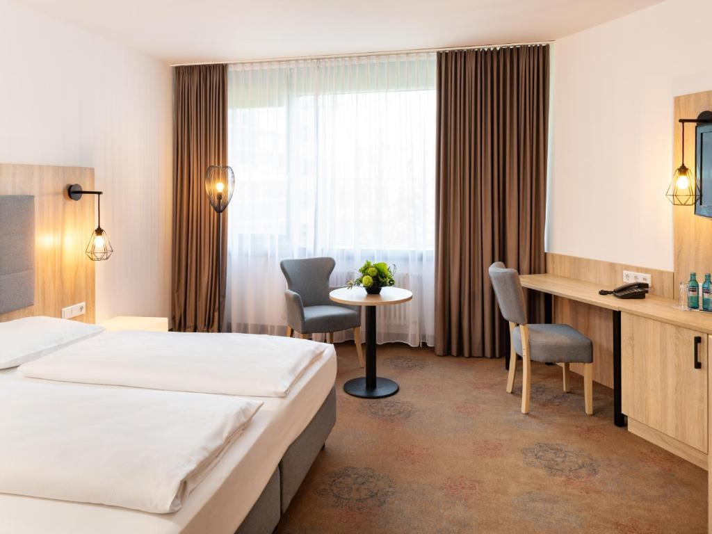A bed or beds in a room at Plaza Hotel & Living Frankfurt