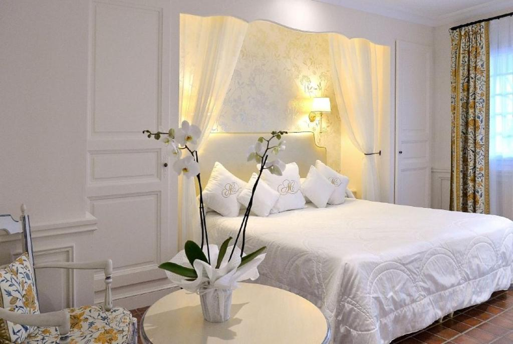 A bed or beds in a room at Auberge de Cassagne & Spa