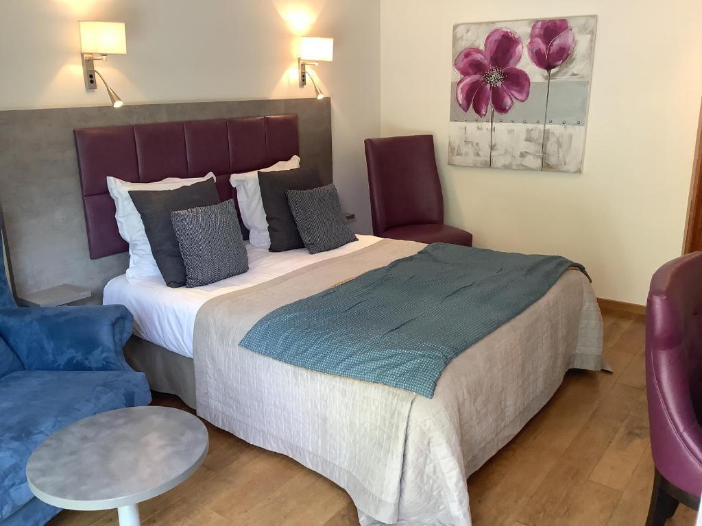 A bed or beds in a room at Citôtel Hôtel Monet