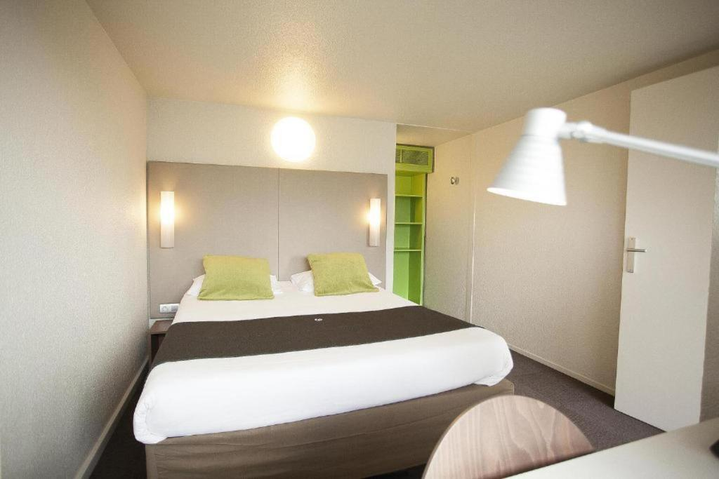 A bed or beds in a room at Campanile Mulhouse - Morschwiller