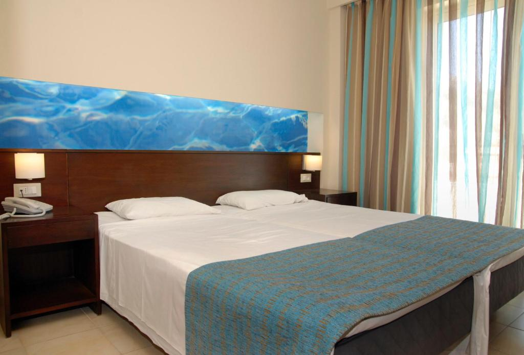 A bed or beds in a room at Troulakis Village Resort - All Inclusive