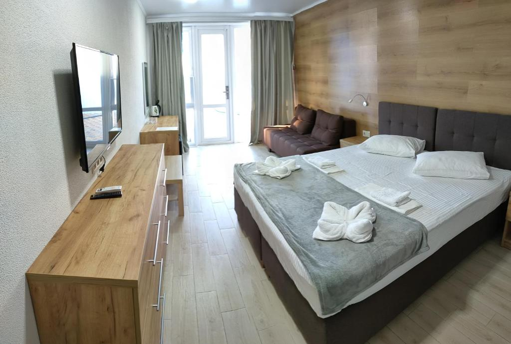 A bed or beds in a room at Aquapark Koblevo Hotel
