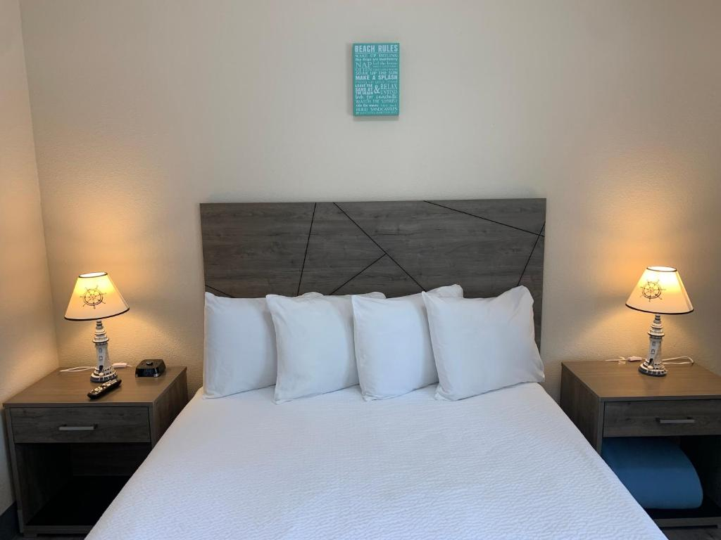 A bed or beds in a room at Coastal Inn and Suites
