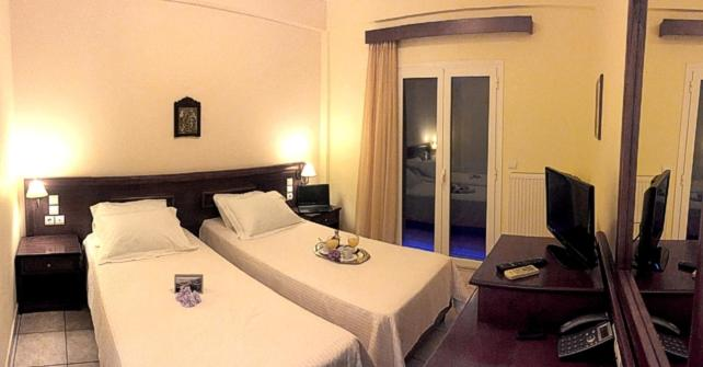 A bed or beds in a room at Venardos Hotel