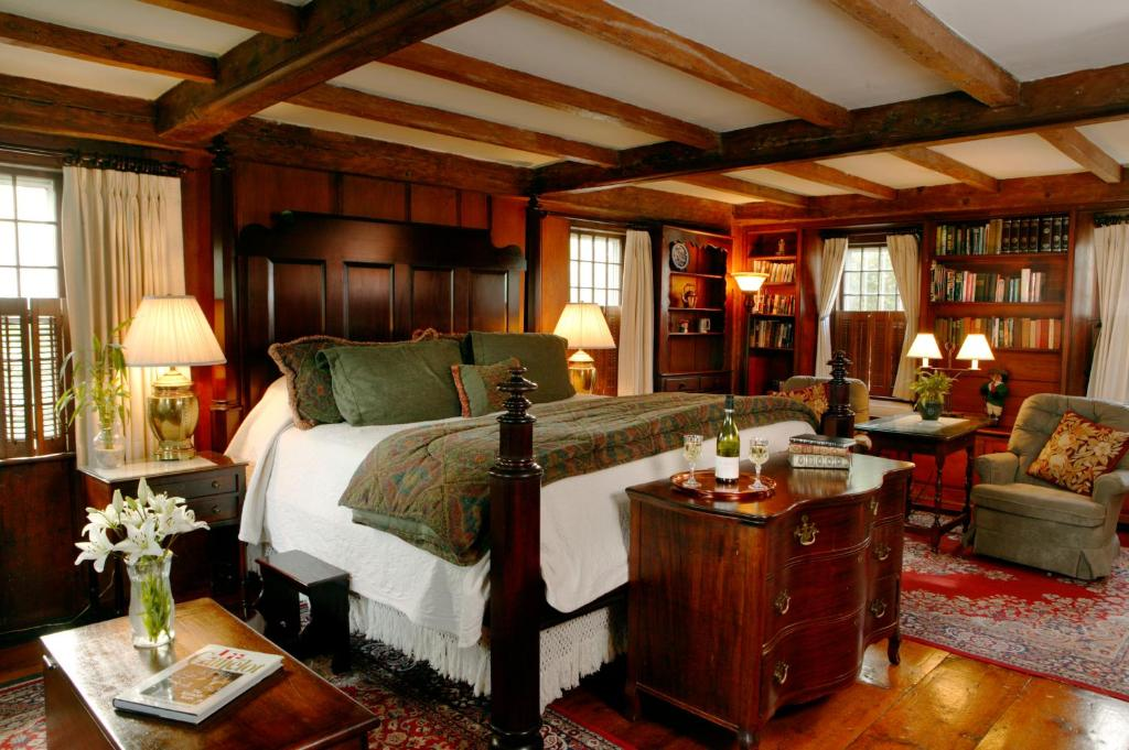 A bed or beds in a room at Captain's House Inn