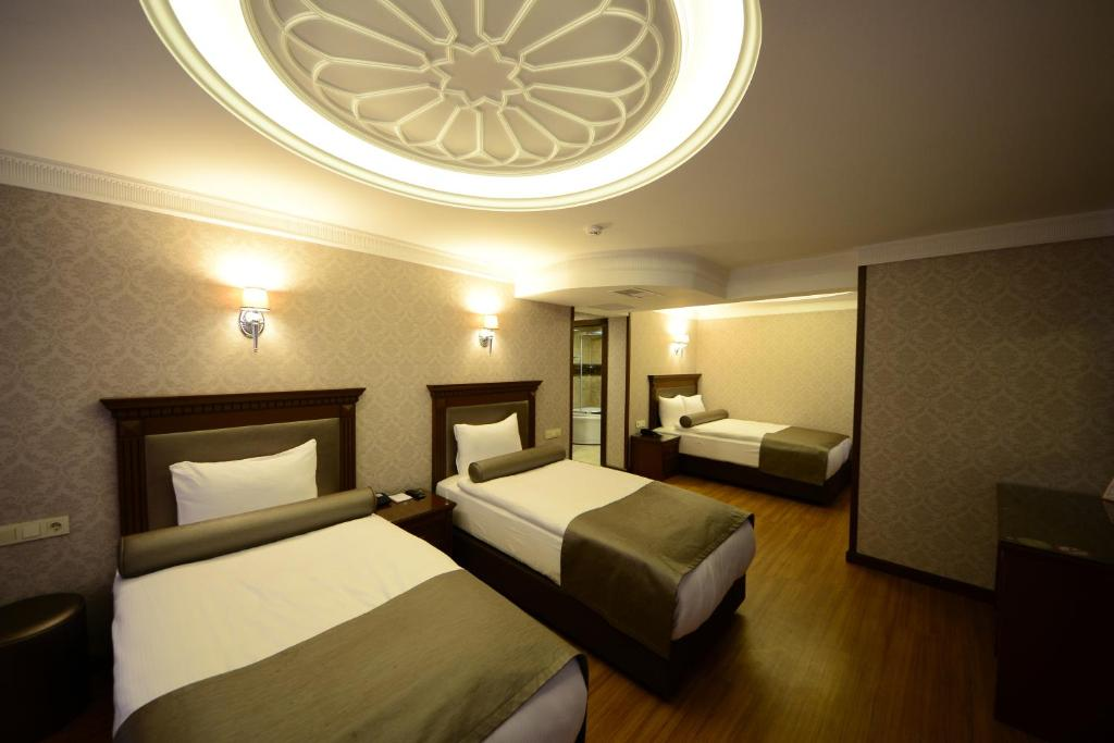 A bed or beds in a room at Grand Bazaar Hotel