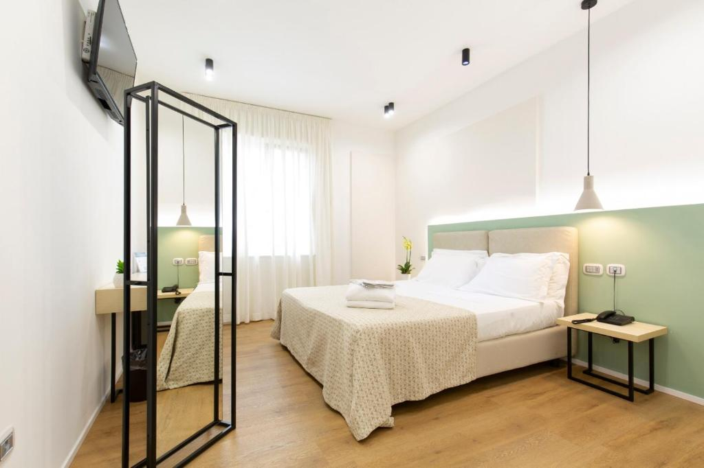 A bed or beds in a room at Plana Hotel