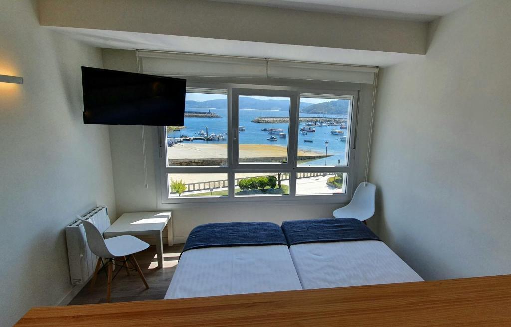 A bed or beds in a room at Apartamentos Costa da Morte Muxia