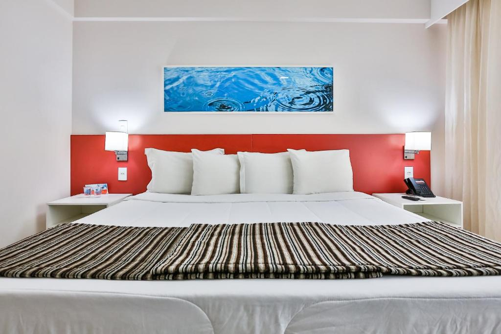 A bed or beds in a room at Ramada Hotel & Suites Campos Pelinca