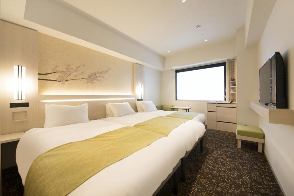 A bed or beds in a room at Hotel Yaenomidori Tokyo