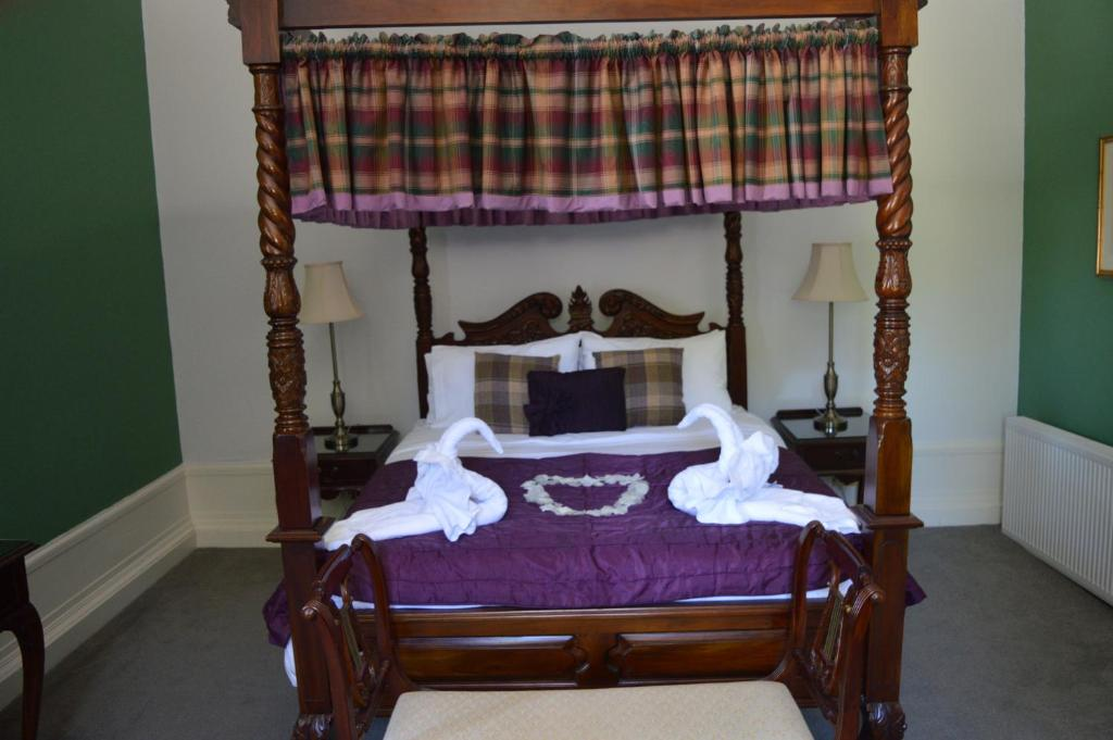 A bed or beds in a room at Bennachie Lodge Hotel
