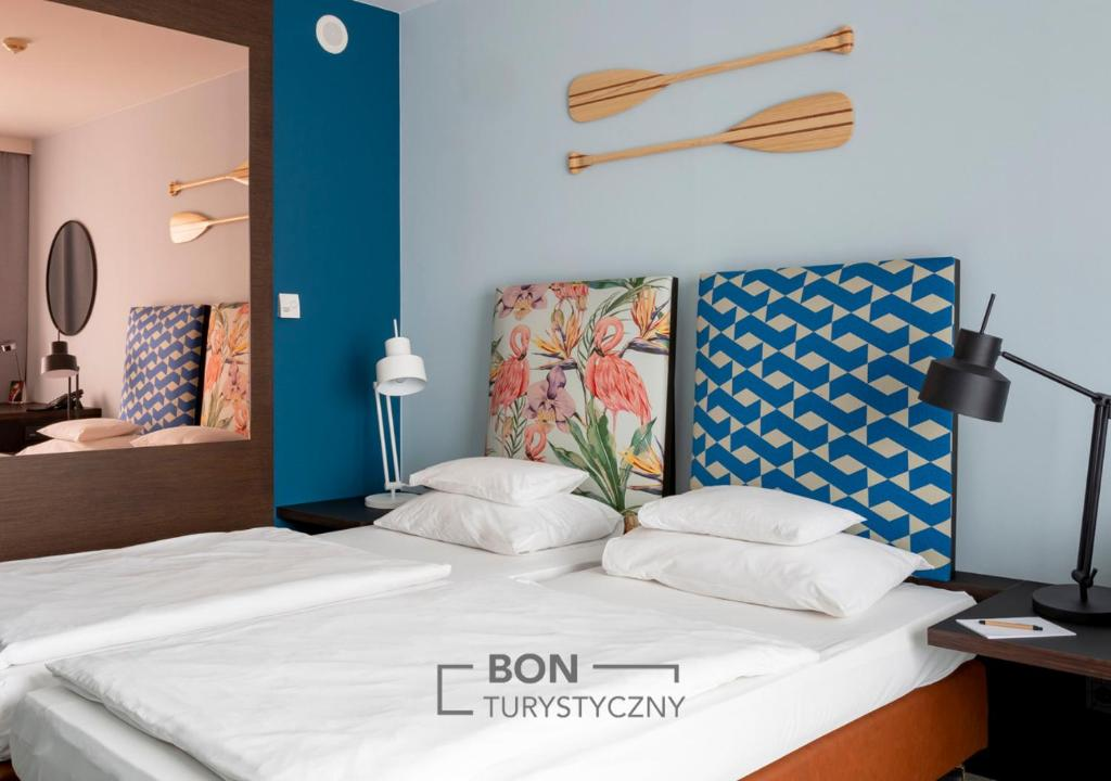 A bed or beds in a room at Vienna House Andel's Cracow