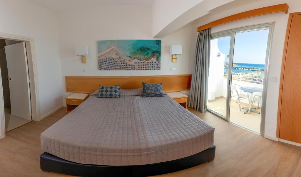 Кровать или кровати в номере Tylos Beach Hotel