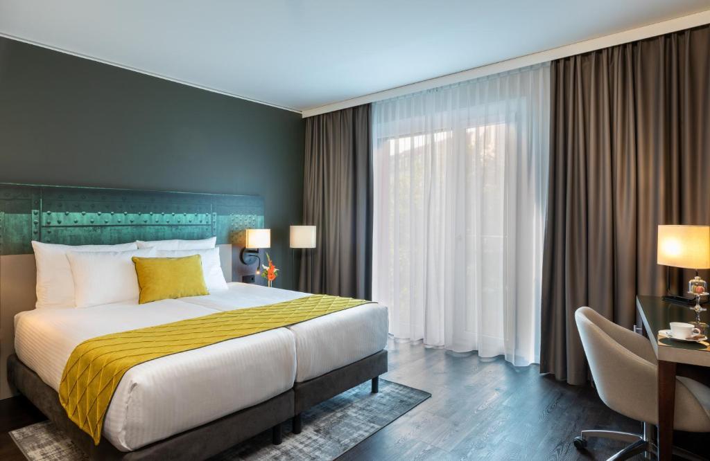A bed or beds in a room at Leonardo Hotel Dortmund