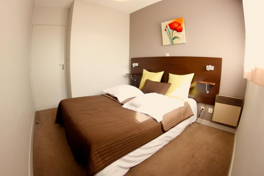 Un ou plusieurs lits dans un hébergement de l'établissement Appart'hotel Les Palatines