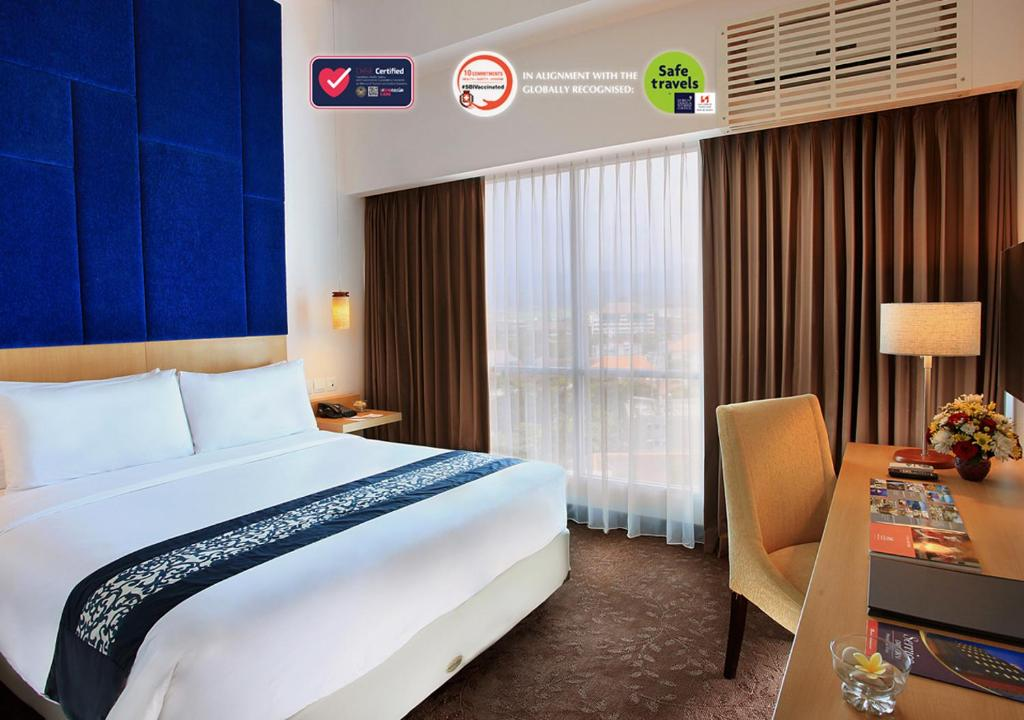 A bed or beds in a room at Swiss-Belinn Malang