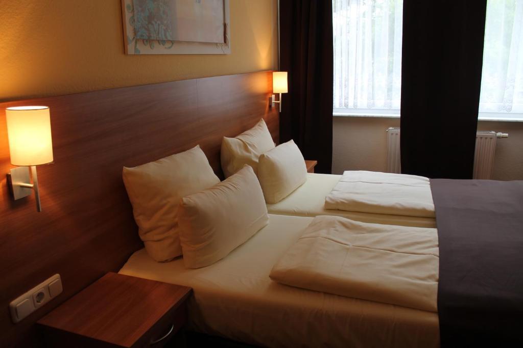 Ein Bett oder Betten in einem Zimmer der Unterkunft Hotel Harburger Hof