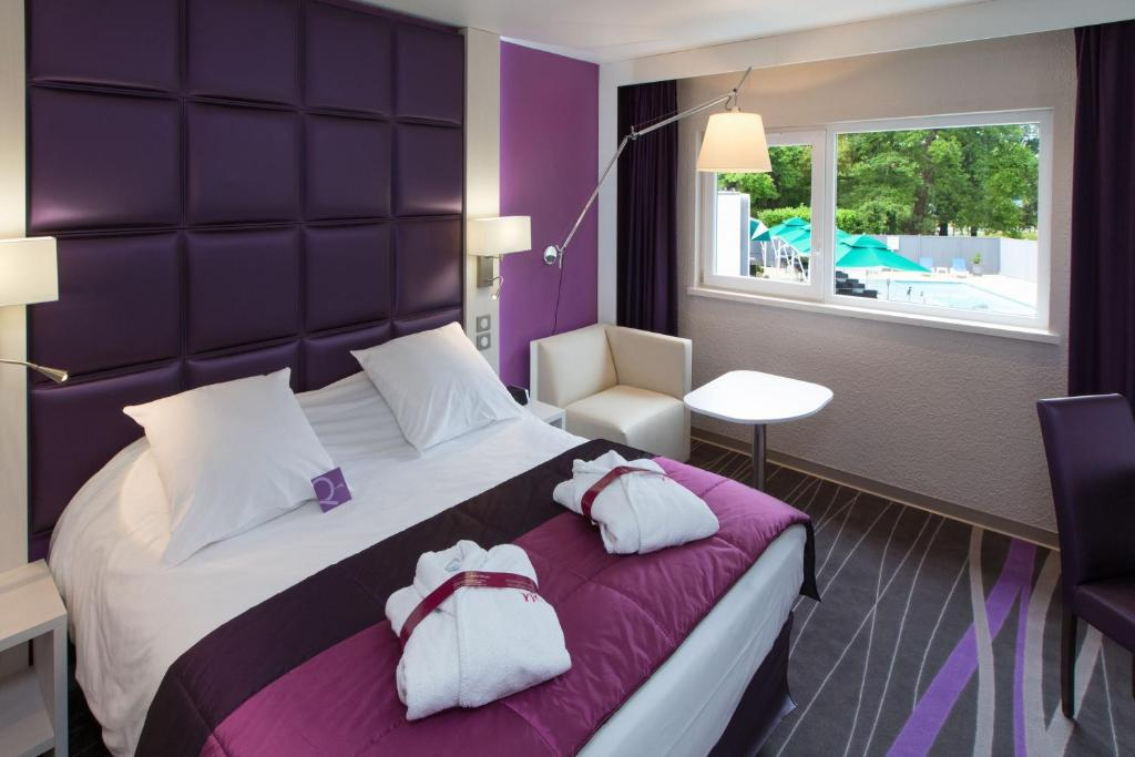 A bed or beds in a room at Mercure Strasbourg Aéroport