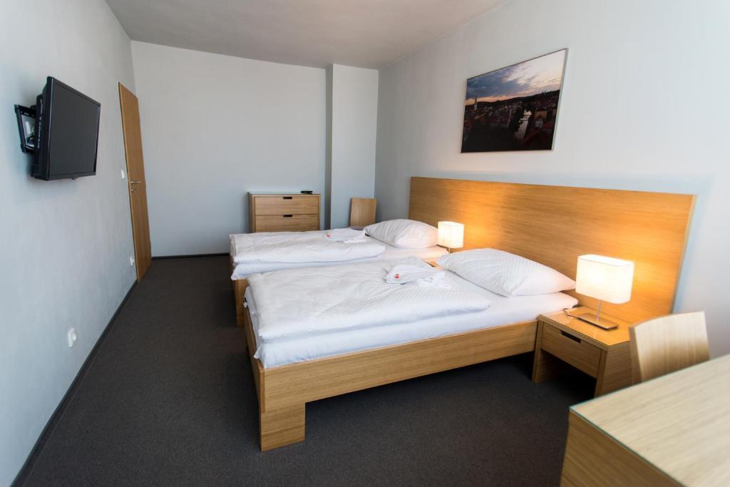 Кровать или кровати в номере Hotel Atom Třebíč