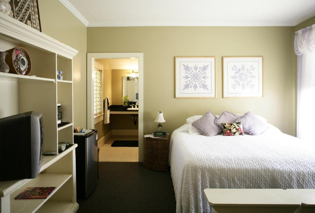 A bed or beds in a room at West Kauai Lodging