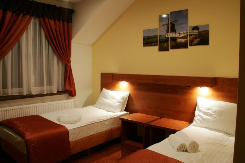A bed or beds in a room at Hotel Kuźnia Oberża Polska