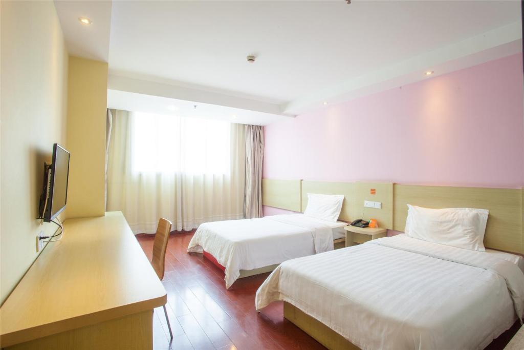 Кровать или кровати в номере 7Days Inn Qingdao Huangdao West Coast Bus Station