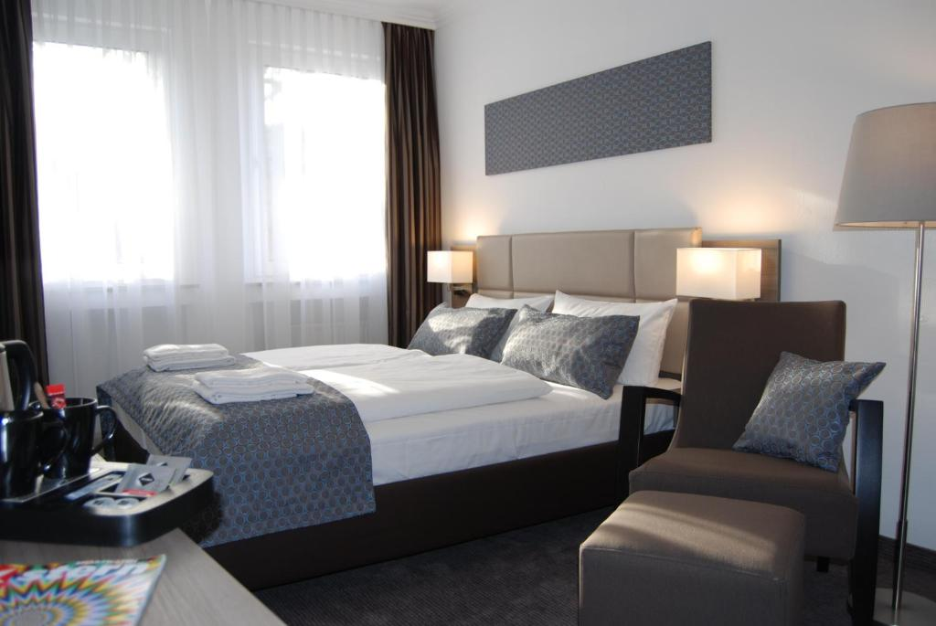 A bed or beds in a room at Dom Hotel Am Römerbrunnen